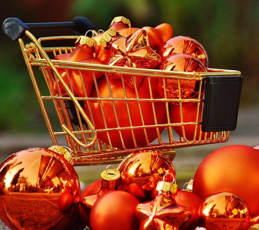 Miniature shopping cart filled with holiday ornaments.