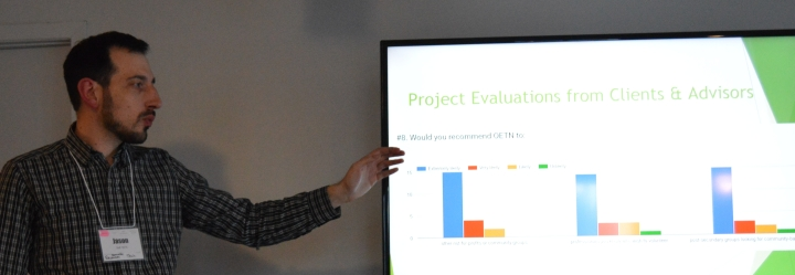 Man in checked shirt gesturing at bar graph in powerpoint presentation.