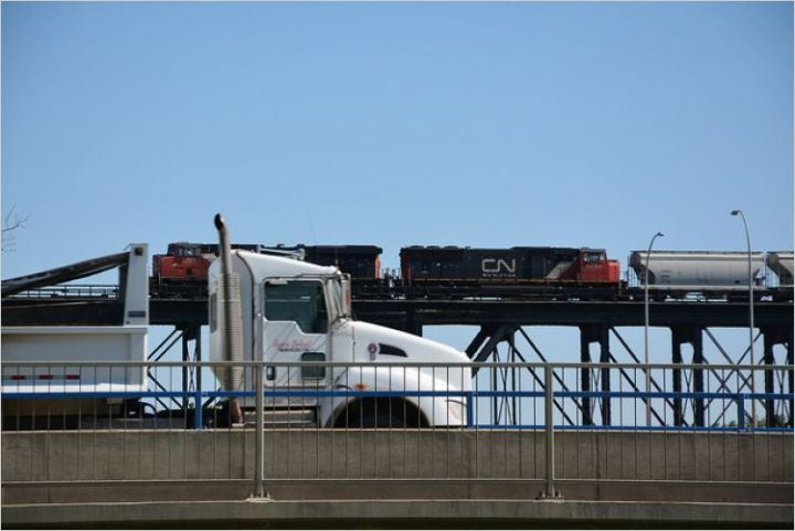 A freight truck and cargo train crossing a bridge.
