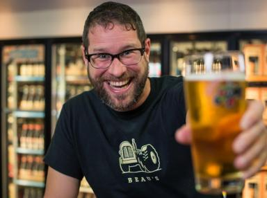 Smiling man in black t-shirt with beer company logo holding a beer up to the camera. Beer is out of focus.