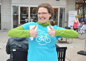 Woman in bright ble tshirt with bicycle logo giving a double thumbs up.