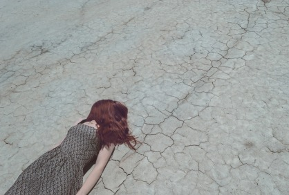 A red haired woman in a dress laying flat on dry cracked soil, seeming sad.